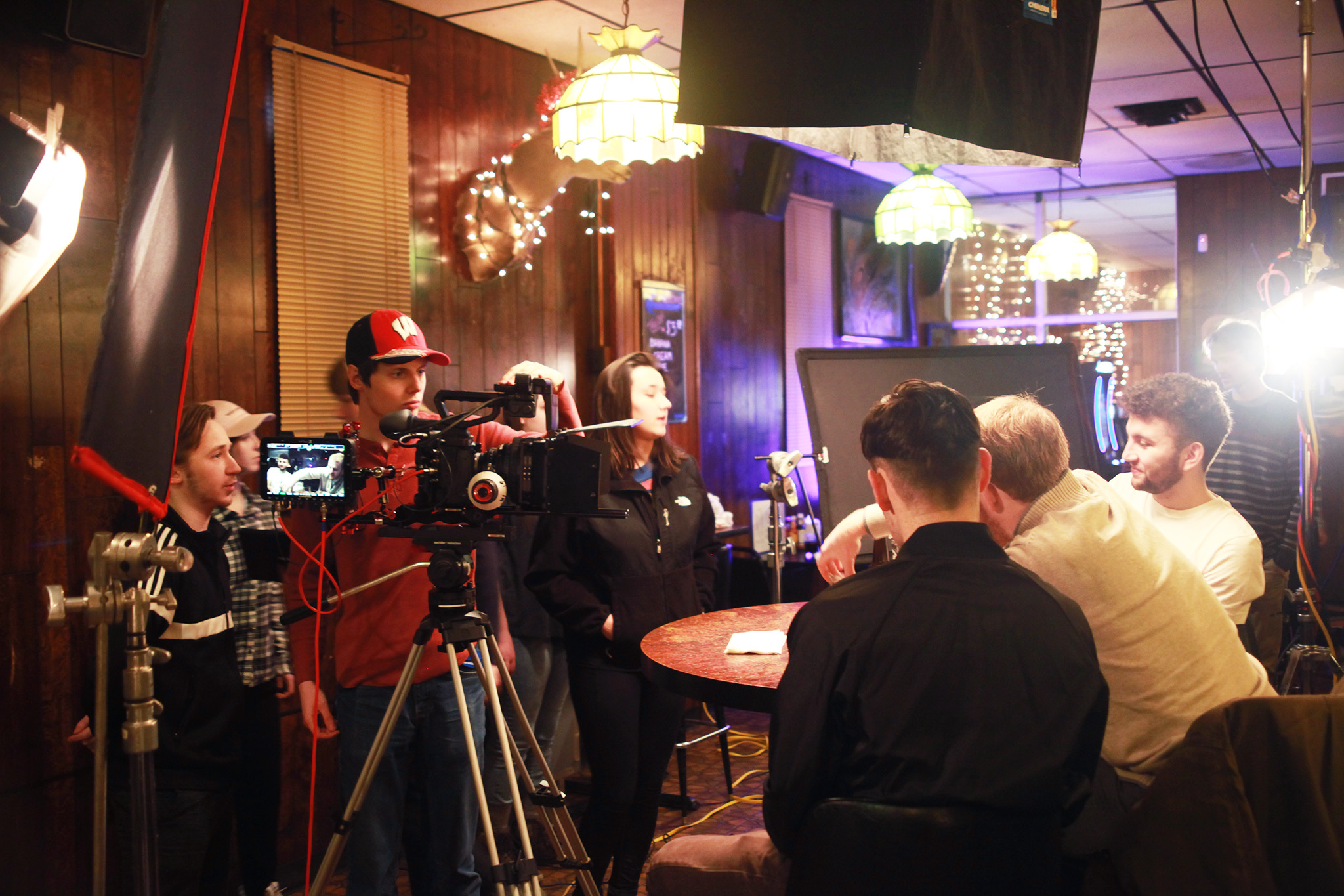 Comm Arts media production students film on location in a bar.