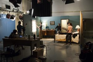 A small student film crew films a dramatic scene in Studio D in Vilas Hall.