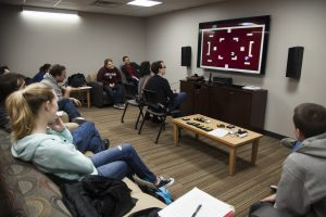 Students in the Living Room Lab look on intensely as two classmates go head-to-head in an Atari video game.