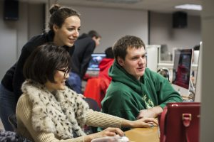 A teaching assistant helps two students editing a video in the Hamel Lab.