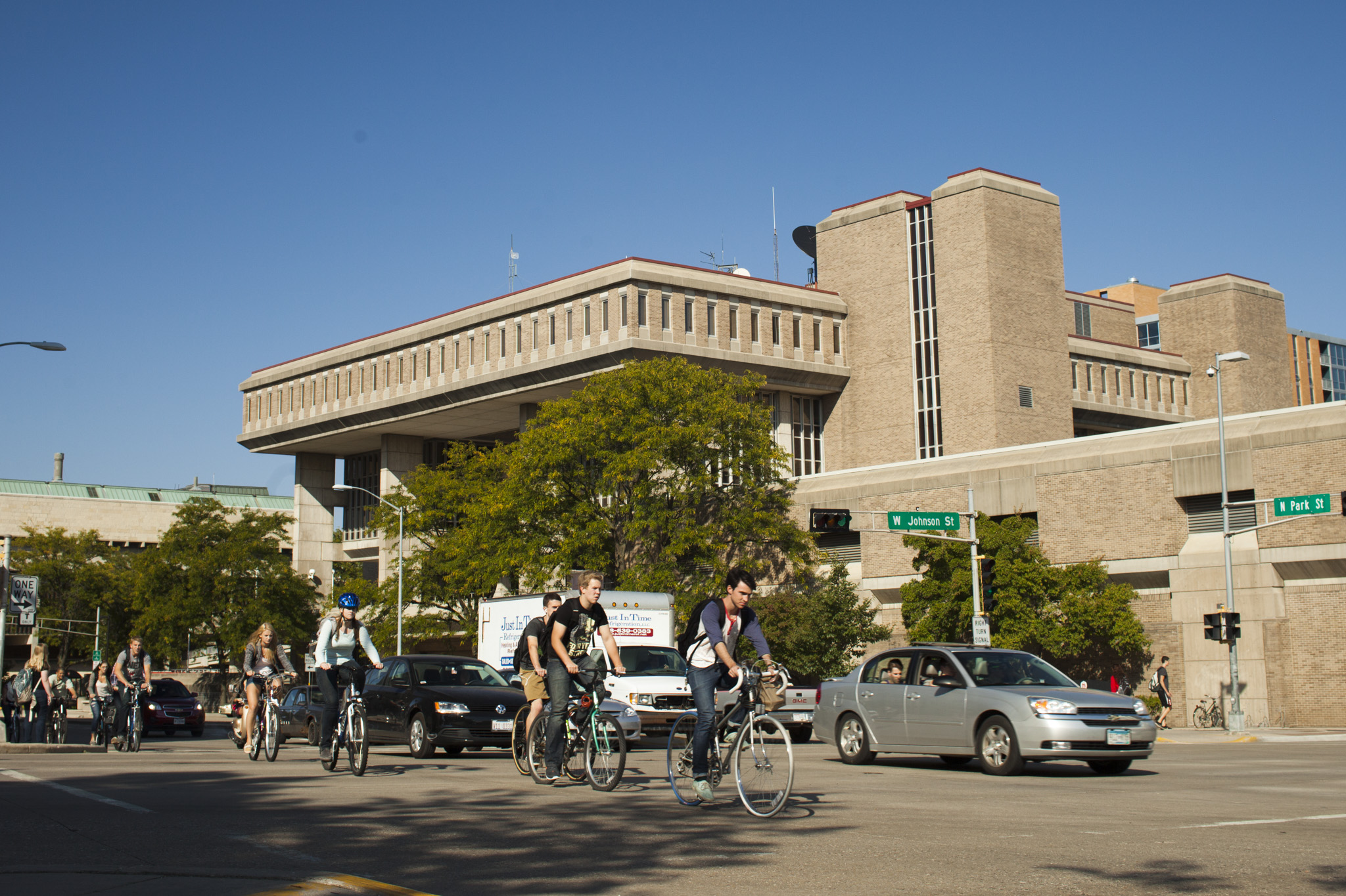 Cyclists and cars pass by Vilas Hall on a summer day.