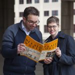 Professors Eric Hoyt and Kelley Conway read an issue of Herald World magazine.